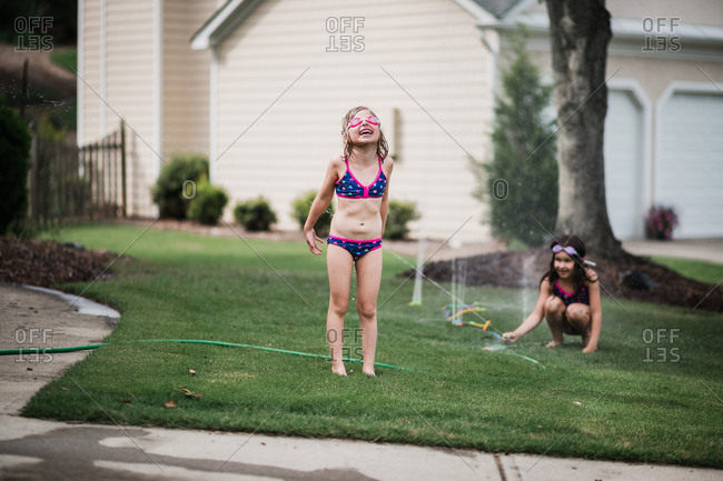 Little girl spraying her sister with a sprinkler