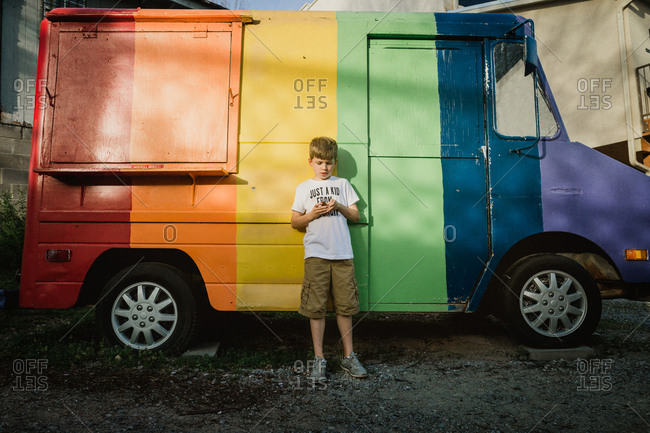 Boy standing in front of a rainbow truck