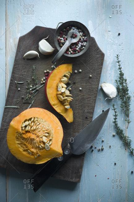 Sliced Hokkaido pumpkin and herbs on wooden board
