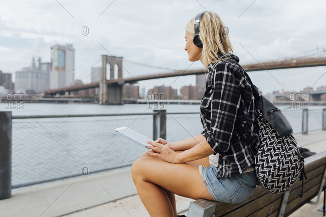 USA- New York City- Brooklyn- young woman sitting at the waterfront with backpack- headphones and tablet