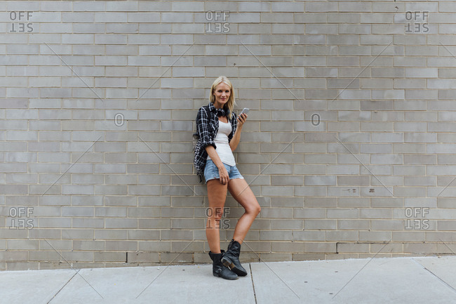 Portrait of young woman with cell phone at brick wall