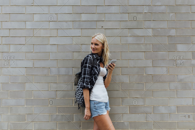 Smiling young woman with cell phone at brick wall