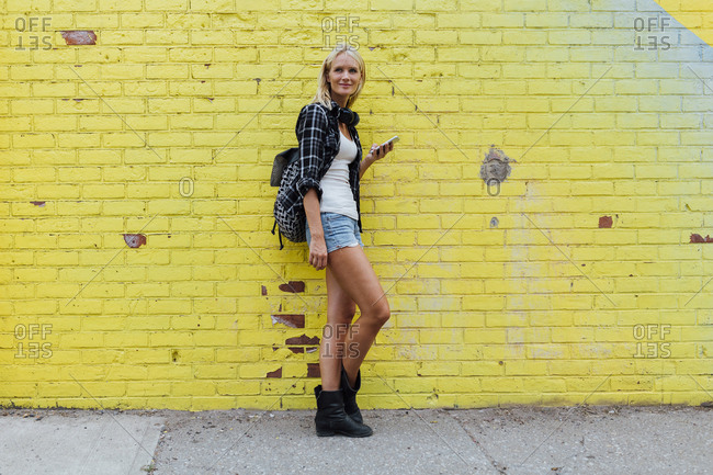 Portrait of young woman with cell phone at yellow brick wall