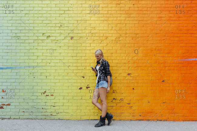 Young woman checking cell phone at colorful brick wall
