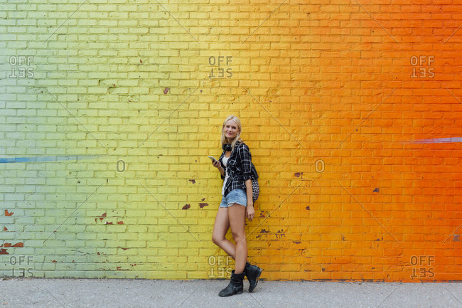 Portrait of young woman with cell phone at colorful brick wall