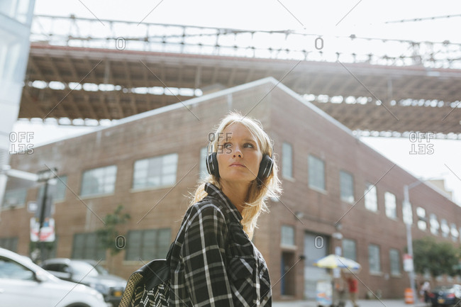 USA- New York City- Brooklyn- young woman listening to music with headphones in the city looking around