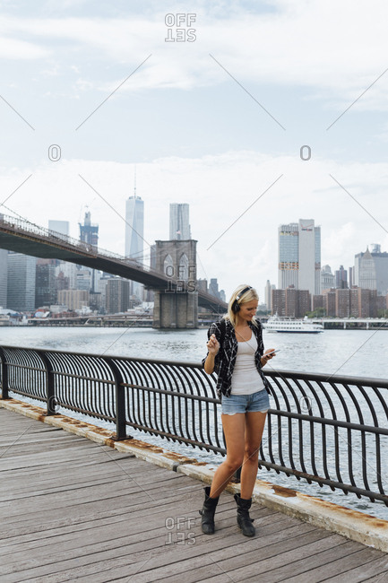 USA- New York City- Brooklyn- young woman standing at the waterfront with headphones and cell phone