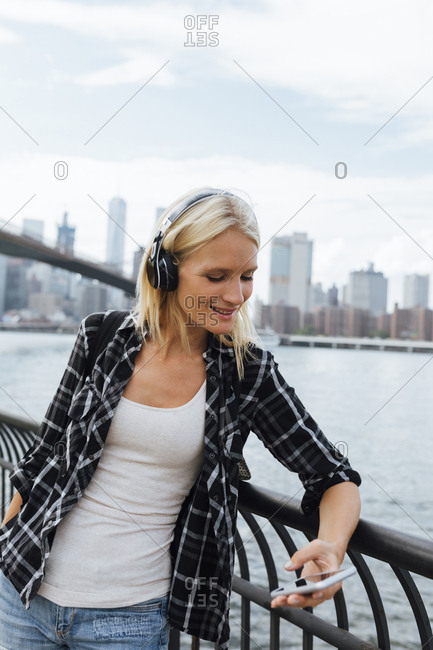 USA- New York City- Brooklyn- smiling young woman standing at the waterfront with headphones and cell phone