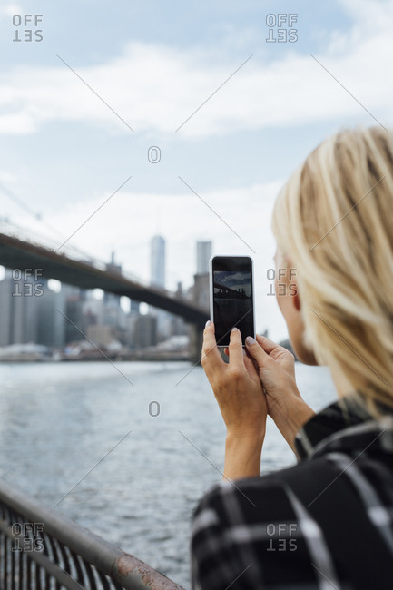 USA- New York City- Brooklyn- young woman at the waterfront taking a cell phone picture of Brooklyn Bridge