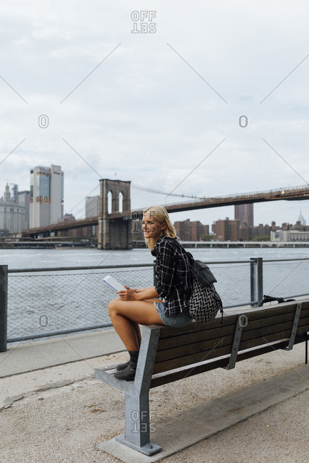 USA- New York City- Brooklyn- smiling young woman sitting at the waterfront with backpack and tablet