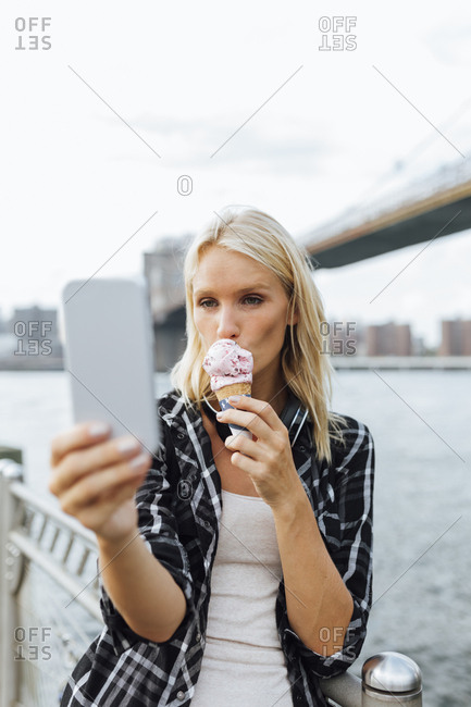 USA- New York City- Brooklyn- young woman standing at the waterfront eating an ice cream and taking a selfie