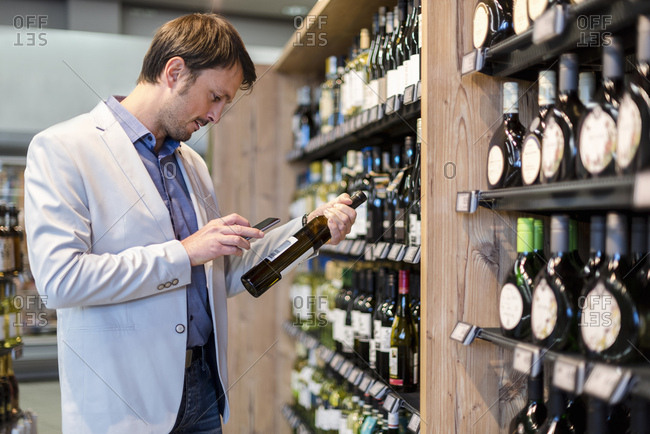 Mature man choosing wine in supermarket- scanning product information ith his smartphone