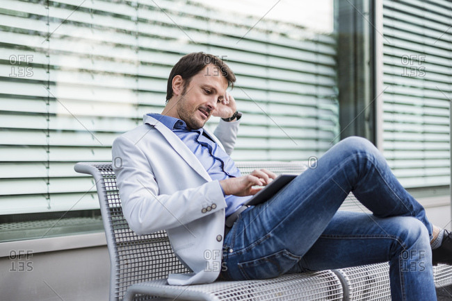 Businessman sitting on a bench- using digital tablet