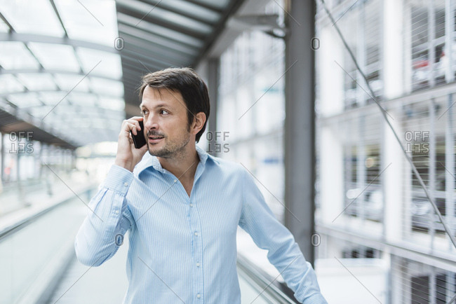 Businessman on a moving walkway- using smartphone