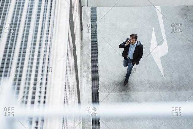 Businessman walking in parking garage- using mobile phone