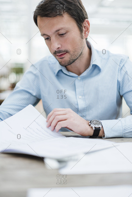Businessman working in office- reading documents