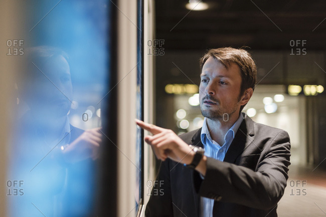 Businessman looking at information panel in the city
