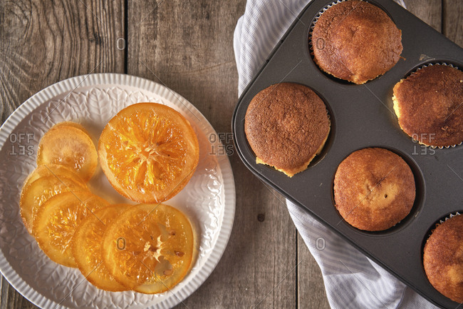Candied orange slices on plate and tray with baked muffins