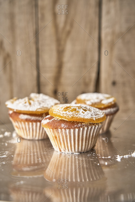Three muffins with candied orange slice and icing sugar on top