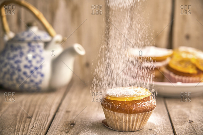 Sprinkling icing sugar on muffin with candied orange on top