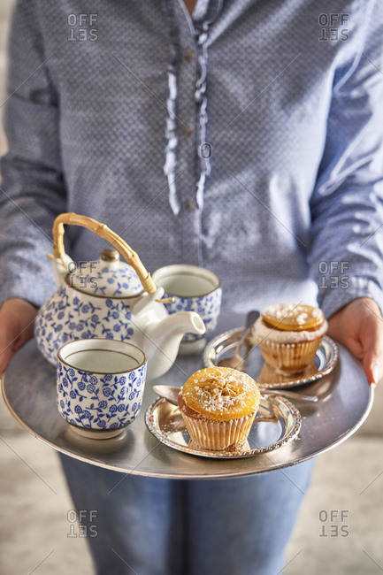 Woman serving fresh muffins and tea on silver platter