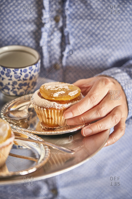 Woman's hand holding muffin with candied orange slice on silver platter