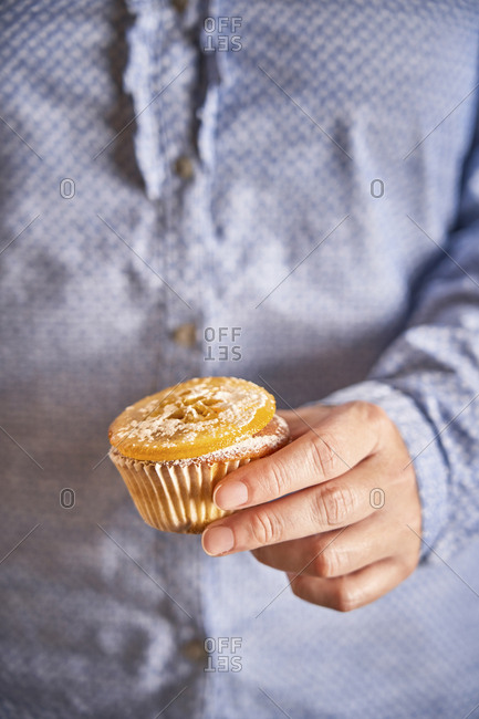 Woman's hand holding muffin with candied orange slice- close-up