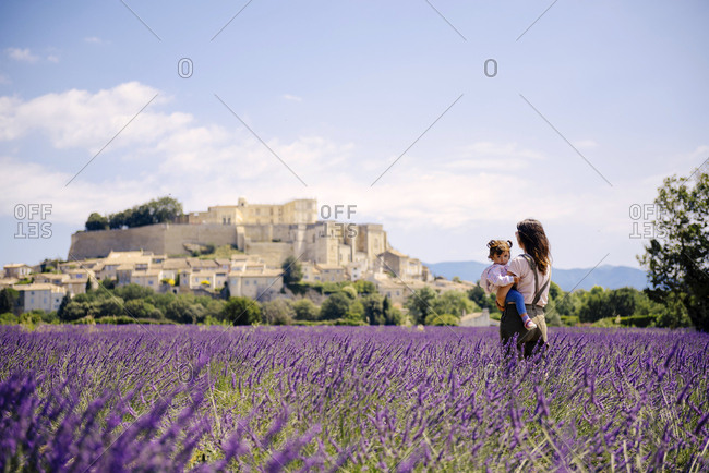 France- Grignan- mother standing in lavender field with little daughter on her arms looking at village