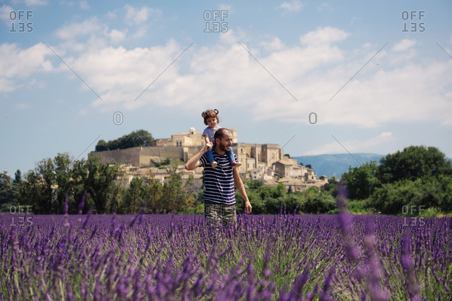 France- Grignan- father carrying little daughter on his shoulders through lavender field