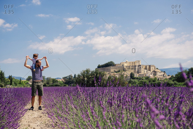 France- Grignan- father standing on foot path between lavender fields with little daughter on his shoulders