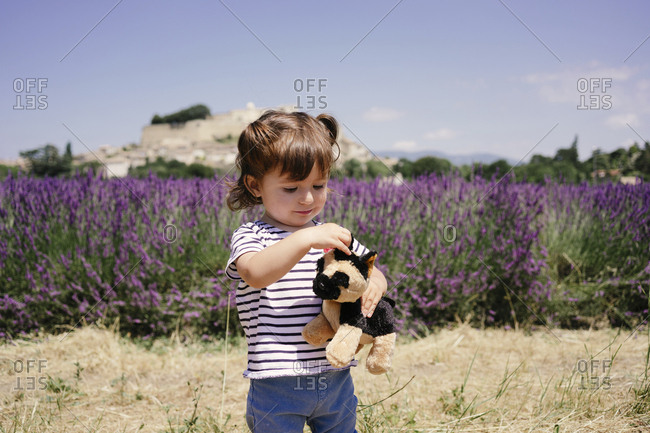 France- Grignan- portrait of baby girl with soft toy outdoors
