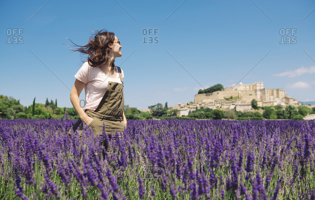 France- Grignan- smiling woman standing in lavender field looking at village