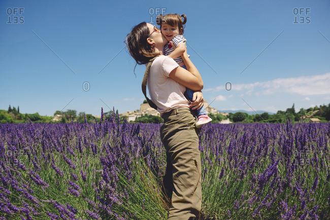 France- Grignan- mother kissing little daughter in lavender field