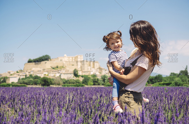 France- Grignan- portrait of happy baby girl together with her mother in lavender field