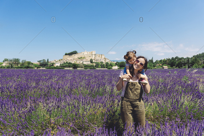 France- Grignan- happy mother carrying her little daughter through lavender field
