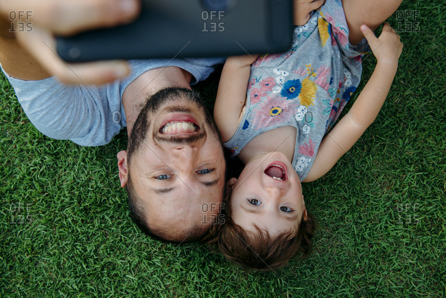 Happy father and daughter taking a selfie with cellphone on green grass