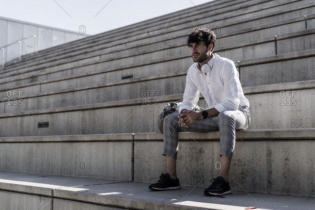 Young man with headphones sitting on stairs outdoors