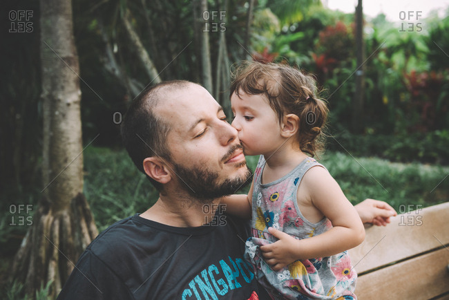 Baby girl kissing her father on cheek in a park