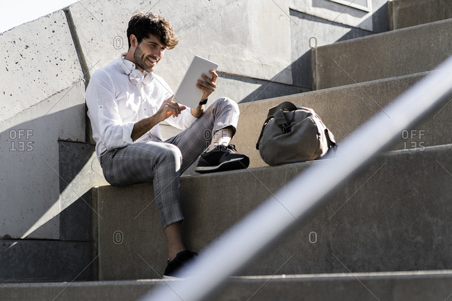 Smiling young man sitting on stairs outdoors using tablet