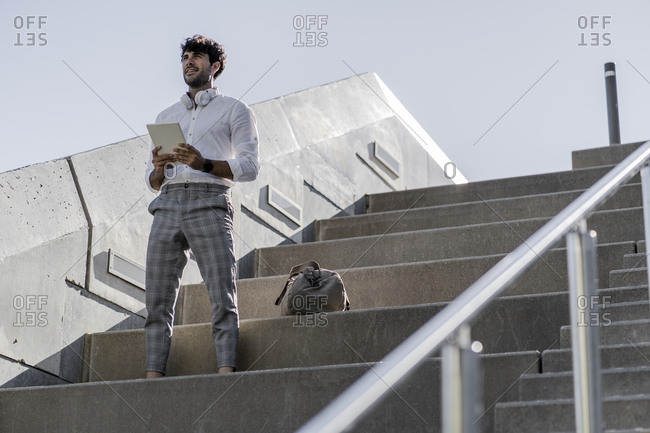 Young man standing on stairs outdoors holding tablet