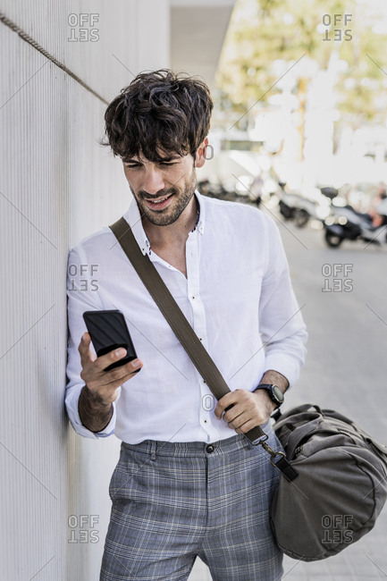 Young man with bag using cell phone in the city