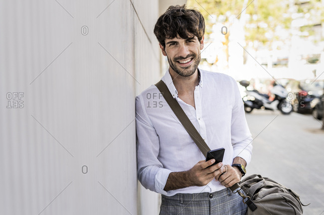 Portrait of smiling young man with bag and cell phone in the city