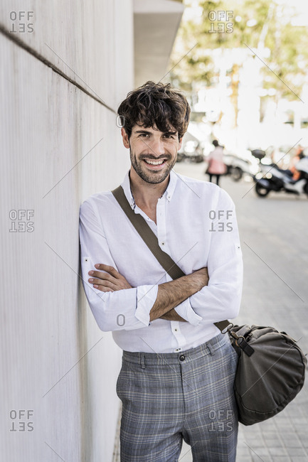 Portrait of smiling young man with bag in the city
