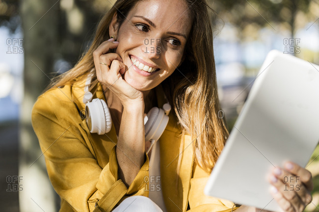 Smiling woman in a park using tablet