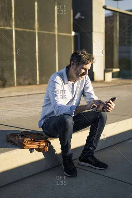 Mature man sitting in the city using cell phone