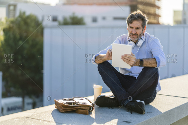 Mature man sitting in the city using tablet