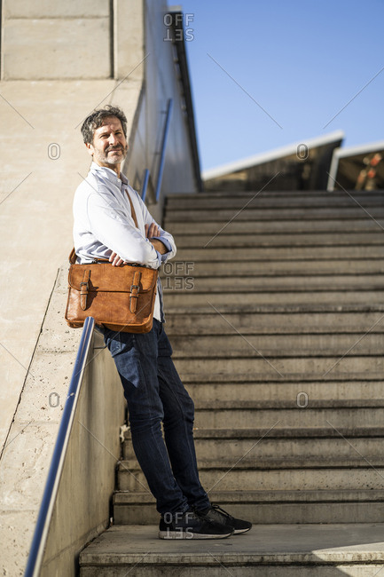 Mature man with a shoulder bag standing on stairs in the city