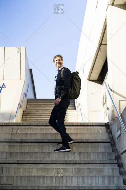 Smiling mature man with a backpack on stairs in the city