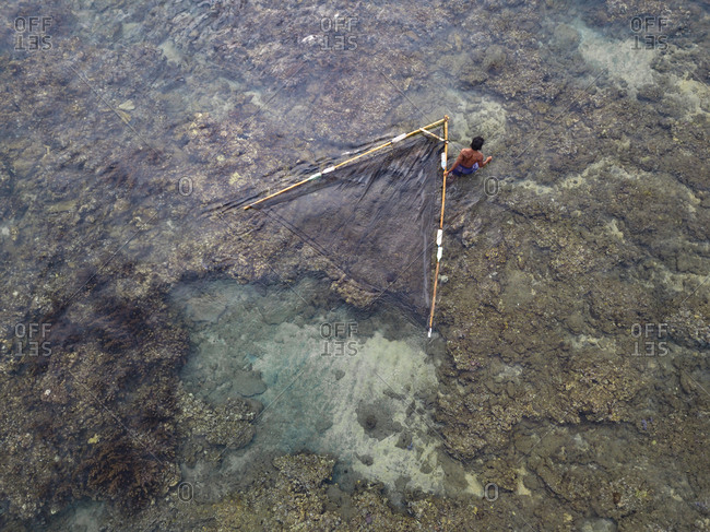 Indonesia- Bali- Aerial view of fisherman with net