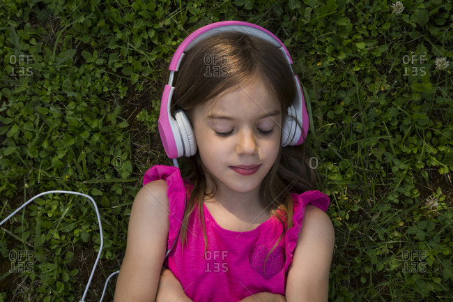Portrait of girl lying on a meadow listening music with pink headphones
